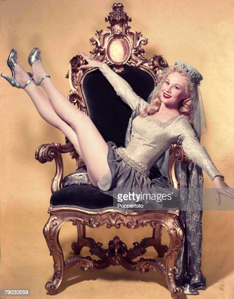 Circa 1950's American musical film actress Virginia Mayo sits back on a throne
