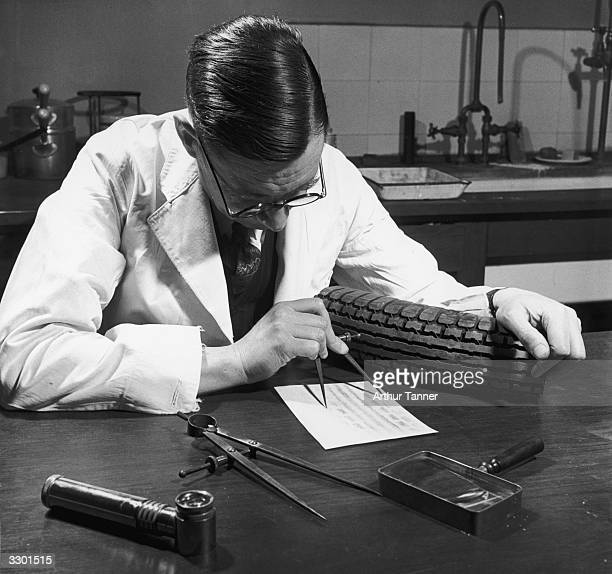 A forensic scientist analysing tyre tracks taken from the scene of a hitandrun car crime