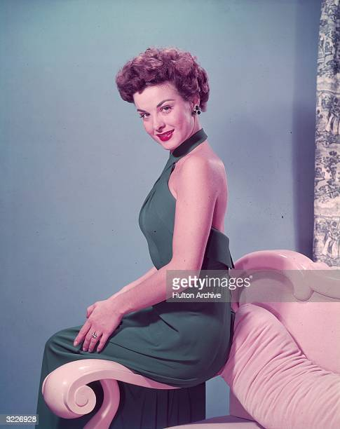 American actor Jean Peters wearing a halter dress sits on the armrest of a sofa in a promotional portrait for director Jean Negulesco's film 'Take...