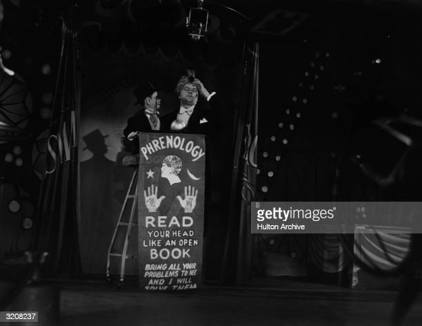 American ventriloquist Edgar Bergen closes his eyes and holds his hand to his head while performing live with his dummy Charlie McCarthy on a circus...