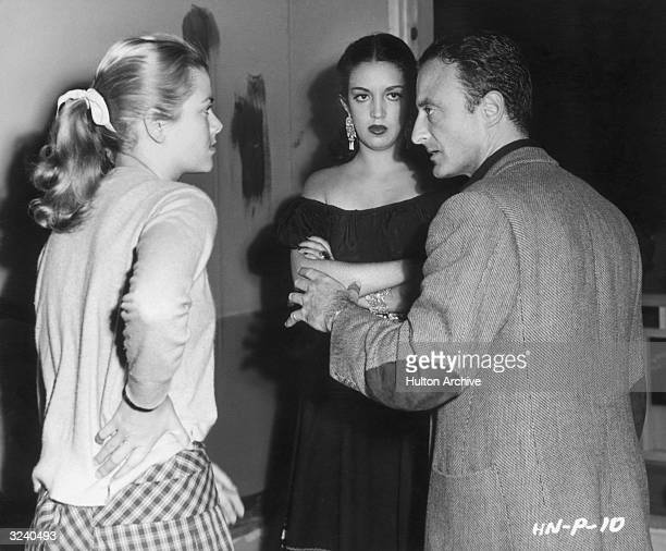 Austrianborn film director Fred Zinnemann explains a scene to American actor Grace Kelly and Mexican actor Katy Jurado during production on the set...