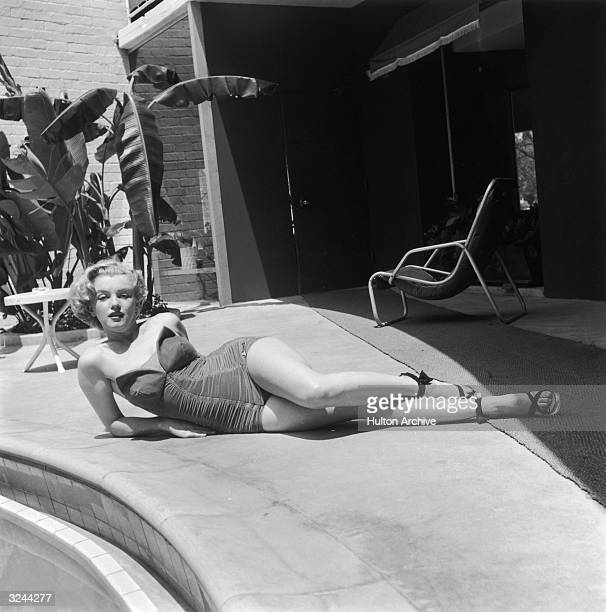 EXCLUSIVE Portrait of American actor Marilyn Monroe lying on a patio next to a swimming pool deck in a strapless bathing suit and high heels