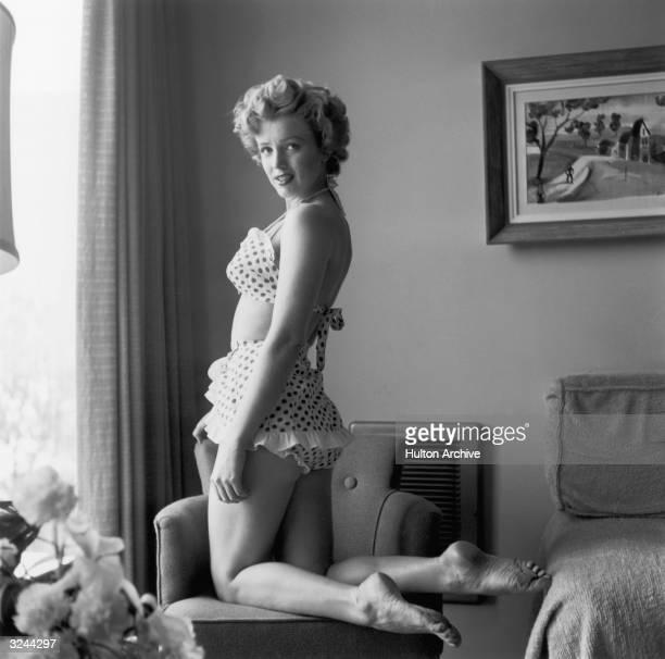 Portrait of American actor Marilyn Monroe kneeling in a chair in a twopiece polka dot bathing suit