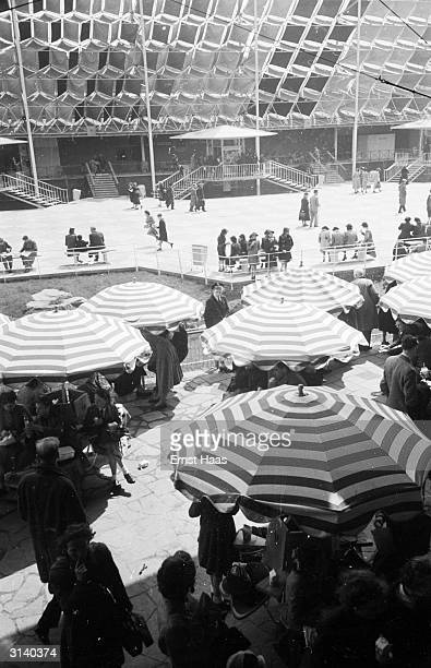 Visitors to the Festival of Britain sit on circular seats under striped umbrellas