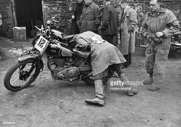 Competitor in the cycling scrambling competition disappears into the workings of his bike, possibly repairing or searching for something.