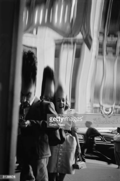 A couple laugh at their distorted reflection in a Hall of Mirrors whilst the Austrianborn American photographer Ernst Haas takes the photograph