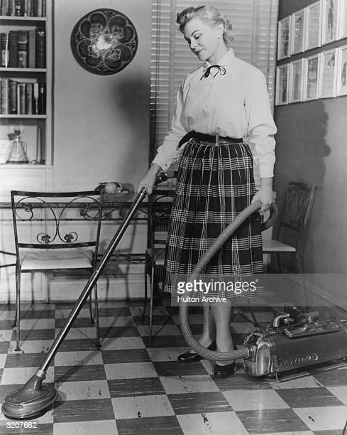 A housewife using an Electrolux vacuum cleaner on a tiled floor