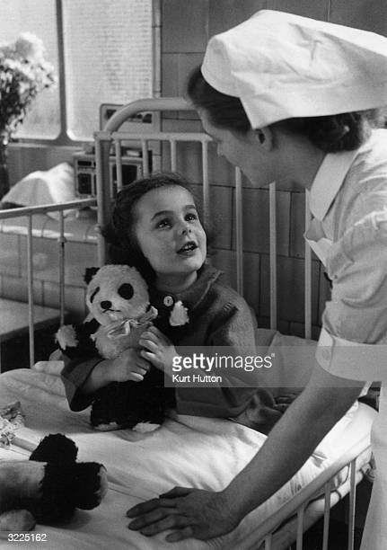 A nurse talking to a young patient and her toy panda while making her rounds at a London Children's Hospital