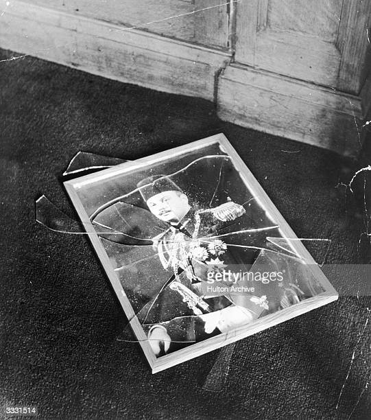A picture of King Farouk I the last reigning king of Egypt lying with its glass broken on a pavement He was forced into exile after the coup of 1952