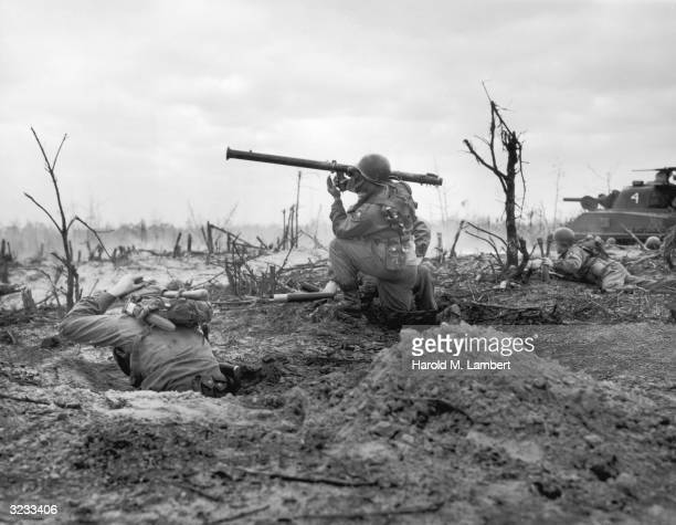 A US or UN soldier prepares to fire a missile launcher across a burnedout field as fellow soldiers duck for cover during a battle in the Korean War...