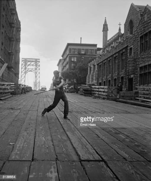 A young boy swinging a baseball bat on a boardwalk in New York