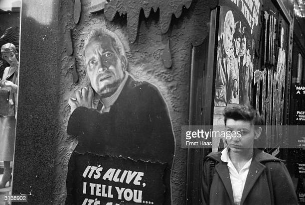 A young woman standing next to a poster for the sciencefiction film 'The Thing from Another World'