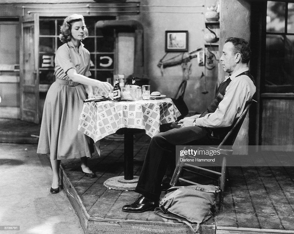 American actor Lauren Bacall reaches for a bottle of beer from a table as her husband, American actor Humphrey Bogart leans back in a chair on a stage set during their performance in the television broadcast of Robert E Sherwood's play, 'The Petrified Forest'.