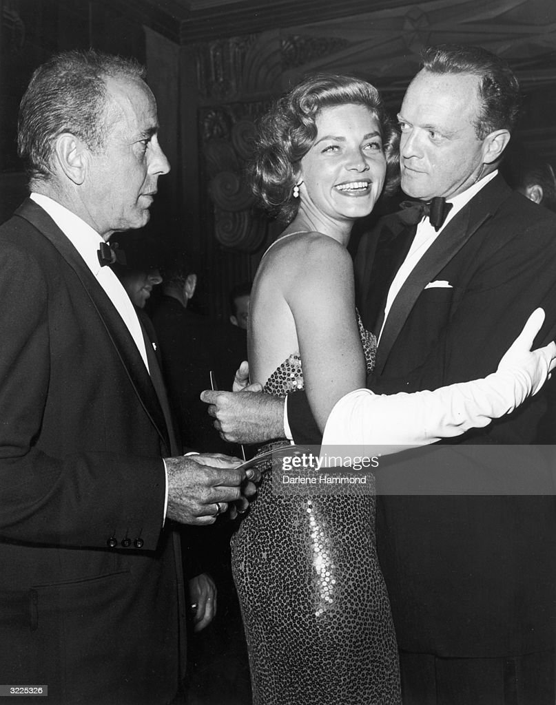 American actors Lauren Bacall and Van Heflin (1910 - 1971) (right) dance at a formal party while Bacall's husband, American actor Humphrey Bogart (1899 - 1957), looks on, early 1950s. Both men wear tuxedos while Bacall wears a sequined dress and long white gloves.