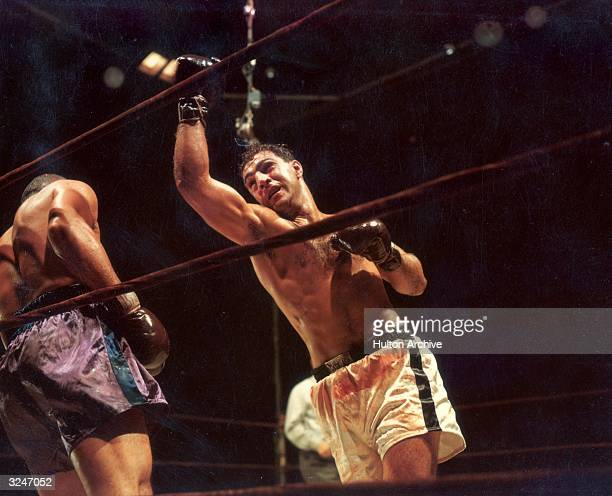 American boxer Rocky Marciano , Heavyweight Champion of the World, follows through on a right swing, which has backed his opponent up against the...