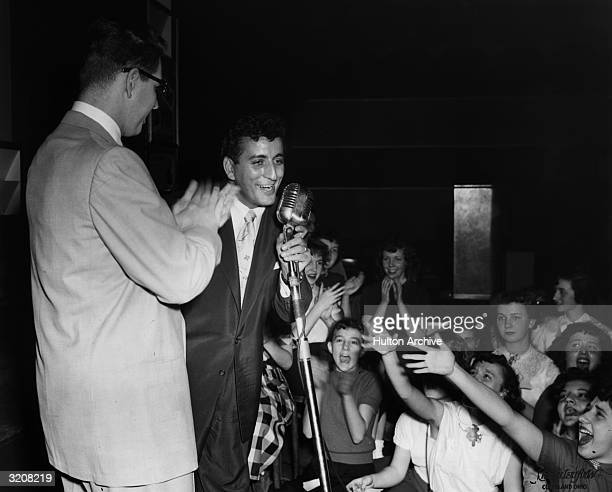 American pop and jazz singer Tony Bennett performs on stage as local radio disc jockey Bill Randall applauds and teenage girls scream in the audience...