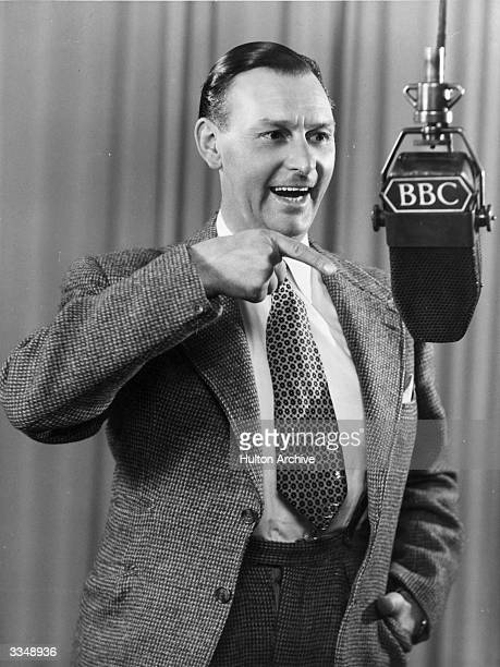 English comedian Al Read at a microphone during a BBC Radio broadcast