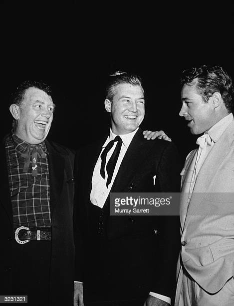 EXCLUSIVE Left to right American actors Andy Devine George Reeves and Guy Madison laugh while standing together in western attire at an event in...