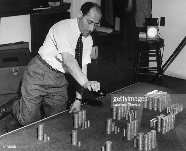 German-born American photojournalist Alfred Eisenstaedt uses a light meter to measure the amount of light on his subject, stacks of coins on a table,...