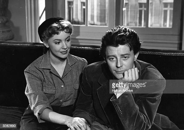Magali Vendeuil is sitting with Gerard Philipe the French actor in a scene from the film 'Les Belles De Nuit' about a discontented teacher who dreams...