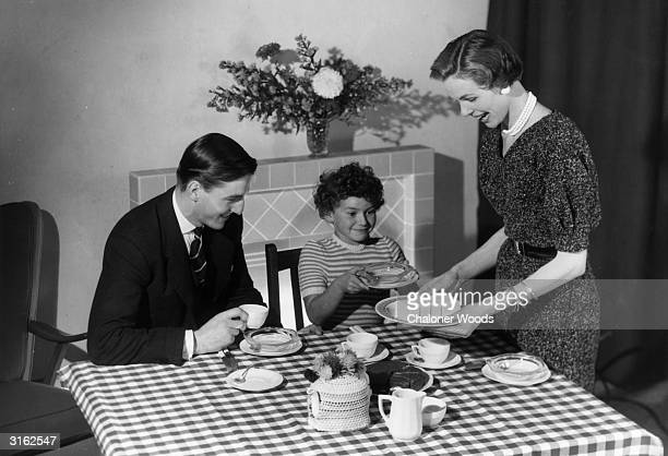 A posed family scene a young couple and their curlyhaired daughter sit down to tea cake and ice cream on a checked tablecloth