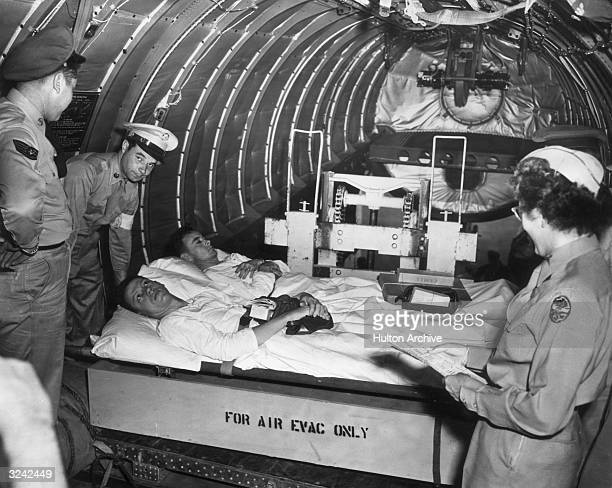 A United States Air Force nurse checks in two American soldiers wounded in battle as they lie on a carloader after being lifted on board the main...