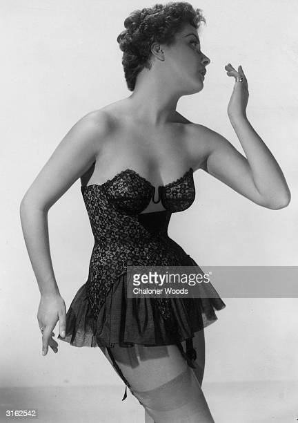 A woman modelling a black lace corset with underwired cups a short frilled skirt and suspenders