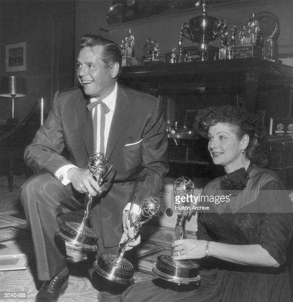 American actor and comedian Lucille Ball and her husband, Cuban-born actor Desi Arnaz smile in front of a trophy case, holding three of their Emmy...