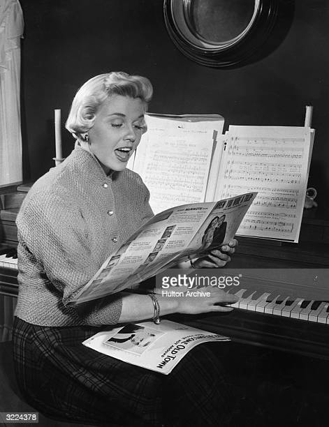 American actor and singer Doris Day sitting at a piano and singing while reading sheet music for 'When You Wore a Tulip ' from 'For Me and My Gal'