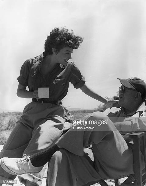 American actor Ava Gardner holding a coffee mug talks to American film director John Ford on the set of the film 'Mogambo'