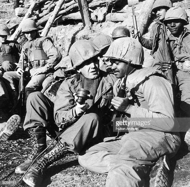 American broadcast journalist Edward R Murrow sits in a trench with a microphone in his hand interviewing an AfricanAmerican US Marine during the...