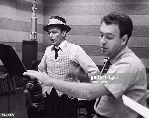 Circa 1953 American singer and actor Frank Sinatra with his conductor and arranger Nelson Riddle during a recording session at Capitol Records