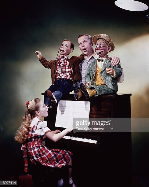 American ventriloquist and comedian Edgar Bergen, flanked by his dummies Mortimer Snerd and Charlie McCarthy, with his daughter, future actor Candice...