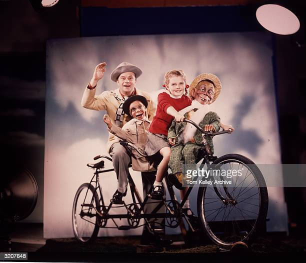 American ventriloquist and comedian Edgar Bergen sitting atop a bicycle built for three with his daughter Candice and his dummies Charlie McCarthy...