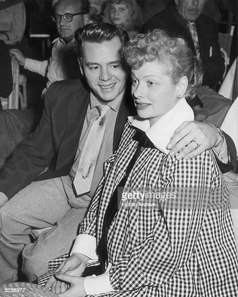 Cuban-born bandleader and actor Desi Arnaz embraces his pregnant wife, American actor and comedian Lucille Ball , while watching a televised football...