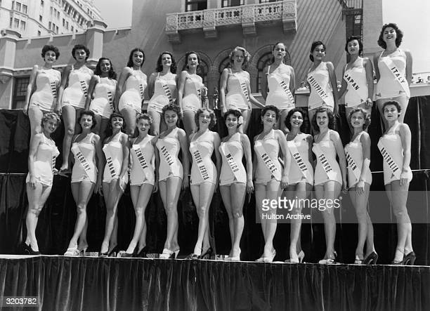 Fulllength group portrait of Miss Universe contestants dressed in bathing suits smiling while standing on a platform in two rows Long Beach California