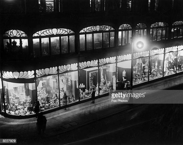 Passersby stop to gaze into the windows of Harrods department store in London