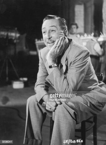 Promotional portrait of American cartoonist and producer Walt Disney smiling while seated in a chair with his chin resting in his hand on the set of...