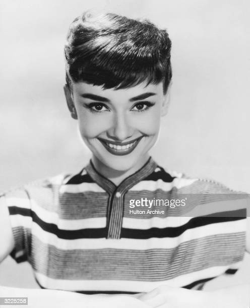 Studio portrait of Belgianborn actor Audrey Hepburn smiling in a striped top