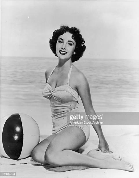Studio portrait of Britishborn actor Elizabeth Taylor sitting on a blanket in the sand next to a beachball in front of an ocean backdrop She wears a...