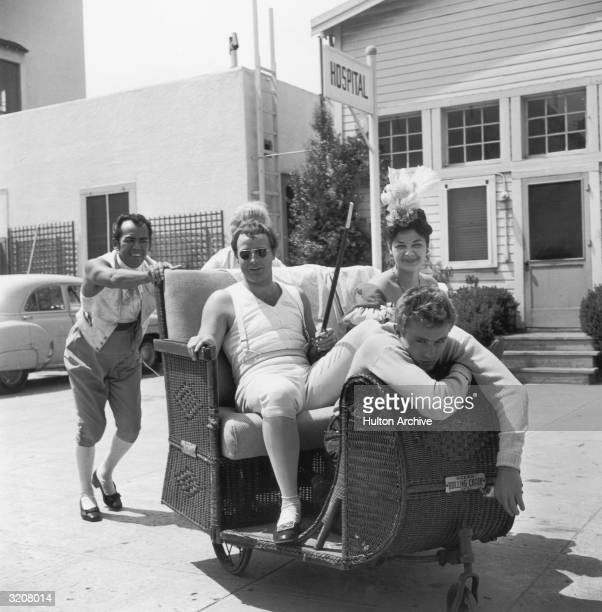 American actors Marlon Brandon James Dean and an unidentified woman are pushed in a wheeled wicker chair by two men on the set of director Henry...