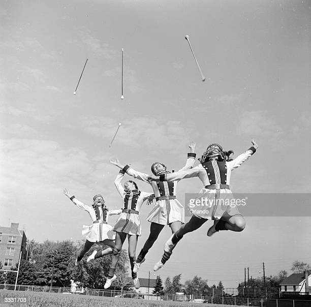 American baton twirlers throw their batons in the air and leap as they practice their routine