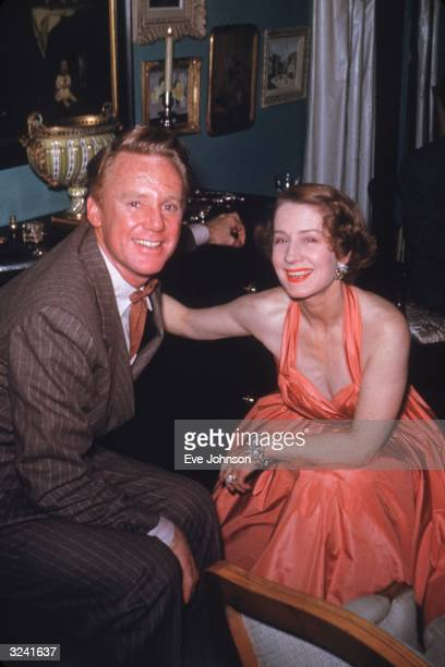 EXCLUSIVE American actor Van Johnson wearing a brown pinstriped suit and Canadianborn actor Norma Shearer wearing an orange gown smile at a party
