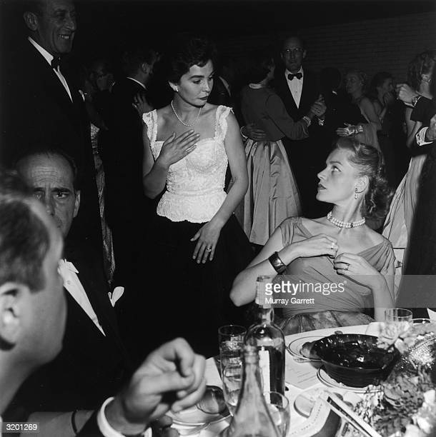 EXCLUSIVE British actor Jean Simmons and American actor Lauren Bacall attend a party following the premiere of American actor and singer Judy Garland...
