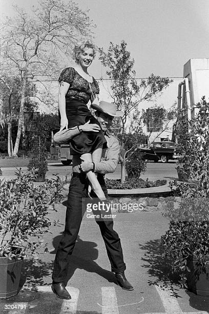 EXCLUSIVE Fulllength image of American actor Marilyn Monroe sitting on the shoulder of actor Don Murray on the set of director Joshua Logan's film...