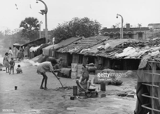 Indian children cooking in front of slum dwellings near the railway station at Calcutta Hundreds of Indians live in this impoverished area