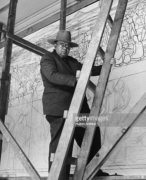 Mexican painter Diego Rivera stands on a wooden platform holding a ladder in front of his mural in progress entitled 'The Great City of Tenochtitlan'...
