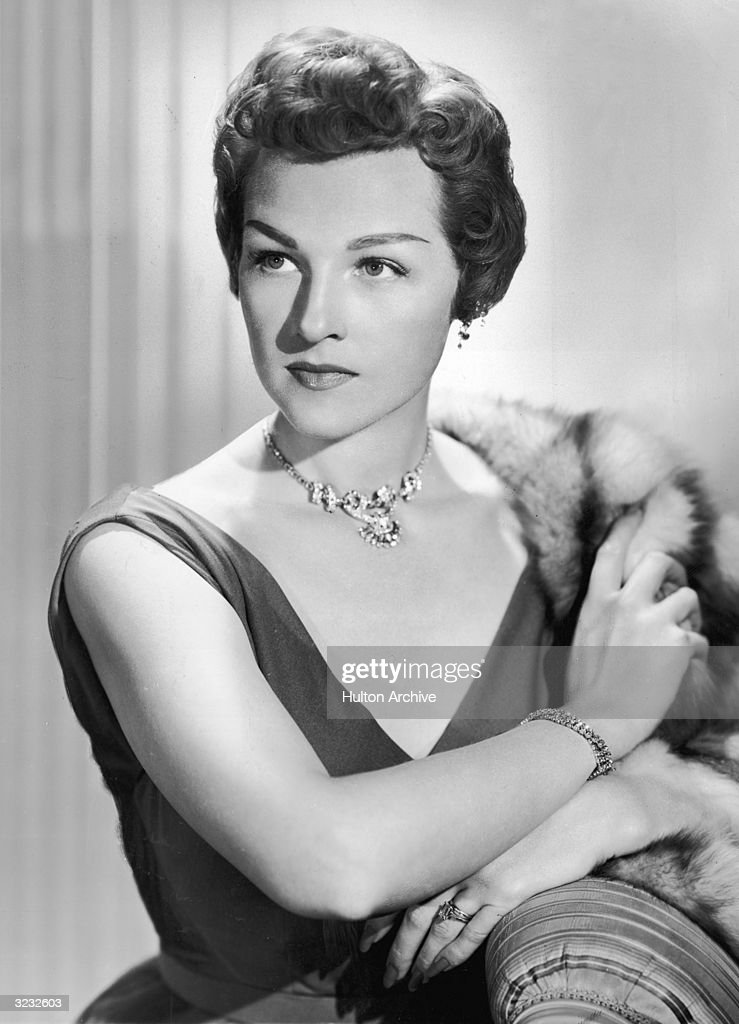 Portrait of American pop and jazz vocalist Jo Stafford wearing a V-neck dress and costume jewelry, posing with a fur stole draped over her shoulder.