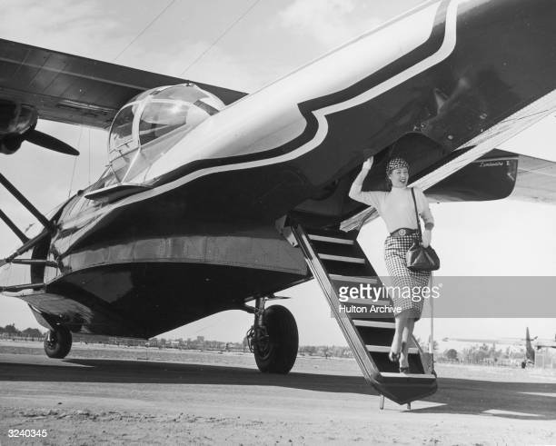 Shirley Buehanon model with the Ed Tabor agency walks down the staircase at the rear of a PBY airplane to exit it