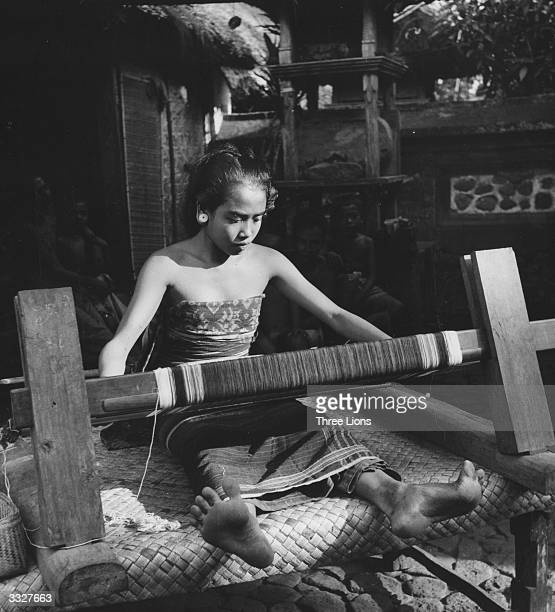 The daughter of a village headman weaving a sarong in Bali